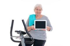 有健身机器和使用的片剂个人计算机女性资深火车 免版税图库摄影