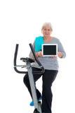 有健身机器和使用的片剂个人计算机女性资深火车 库存图片