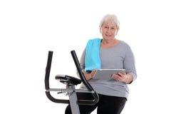 有健身机器和使用的片剂个人计算机女性资深火车 免版税库存照片