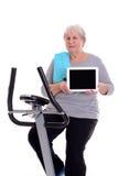 有健身机器和显示的片剂个人计算机女性资深火车 免版税库存图片