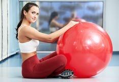 有健身球的愉快的健康妇女 免版税图库摄影
