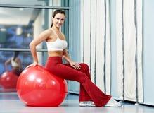 有健身球的愉快的健康妇女 免版税库存图片