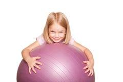 有健身球的愉快的小女孩。 库存照片