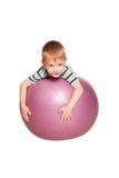 有健身球的愉快的小男孩。 库存照片