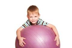 有健身球的愉快的小男孩。 免版税库存图片