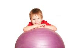 有健身球的愉快的小男孩。 免版税图库摄影