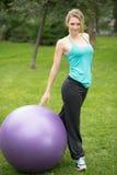 有健身球的年轻愉快的妇女,室外 免版税库存照片