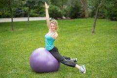 有健身球的年轻愉快的妇女,室外 免版税图库摄影