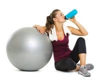 有健身球饮用水的健身少妇 免版税库存图片