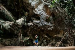 有偶然布料的年轻亚裔男性摄影师在森林洞t 库存照片