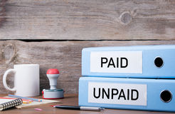 有偿和未付 在书桌上的两种黏合剂在办公室 企业bac 图库摄影