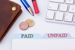 有偿和未付 在白色办公室表上的文件夹记数器 免版税库存照片