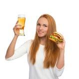 有储藏啤酒杯子的愉快的少妇和汉堡将hambur夹在中间 免版税库存照片