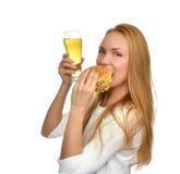 有储藏啤酒杯子的愉快的少妇和汉堡将hambur夹在中间 库存图片
