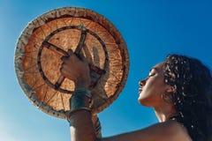 有僧人鼓户外和演奏的种族音乐美丽的年轻女人 库存图片