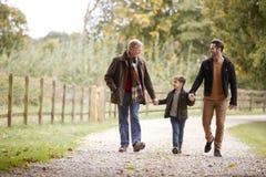 有儿子和孙子的祖父秋天步行的在一起乡下 免版税图库摄影