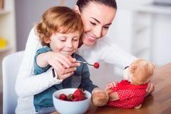 有儿子哺养的玩具熊的母亲 免版税图库摄影