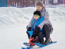 有儿子的愉快的妈妈乘坐从山的一个雪撬 免版税库存照片