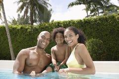 有儿子的愉快的父母游泳池的 免版税库存照片