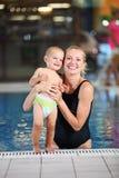 有儿子的新母亲游泳池的 免版税库存图片