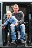 有儿子的残疾人轮椅升降式的 免版税库存照片