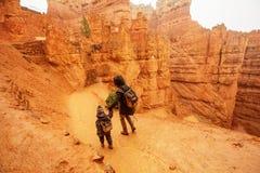 有儿子的母亲在布莱斯峡谷国立公园,犹他,美国步行 免版税库存图片