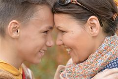 有儿子的母亲在秋天公园 免版税库存照片