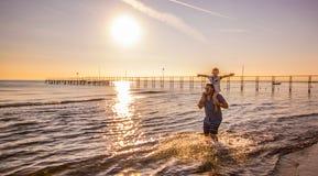 有儿子的爸爸他的肩膀的在水中走在海 免版税库存照片