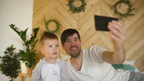 有儿子的年轻微笑的父亲在拍与智能手机照相机的床上selfie照片 影视素材