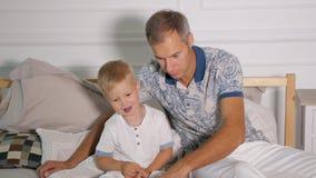 有儿子观看的膝上型计算机的人在床上 影视素材