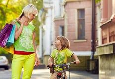 有儿子走的城市街道的妇女 免版税库存照片
