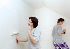 有儿子绘画墙壁的主妇对白色 库存照片