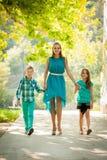 有儿子adn女儿的母亲步行的在公园 免版税库存照片