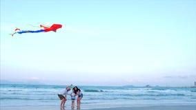 有儿童发射的幸福家庭使用与更旧的风筝的风筝、母亲父亲和女儿在海洋背景中 股票录像