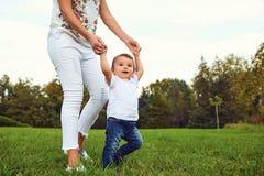 有儿童步行的母亲在公园在夏天 免版税库存照片