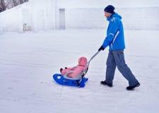 有儿童步行的父亲在冬天在雪的爬犁 免版税库存图片