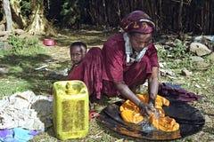 有儿童洗涤的洗衣店的埃赛俄比亚的母亲在家 库存照片