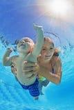 有儿童游泳和潜水的母亲水下在水池 免版税库存图片