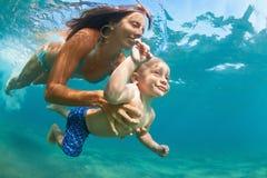 有儿童游泳的母亲水下与乐趣在海 免版税库存图片