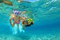 有儿童游泳的母亲水下与乐趣在海 免版税图库摄影