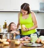 有儿童烹调的微笑的母亲 库存照片