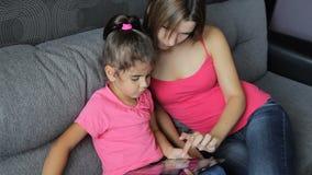 有儿童用途的妇女片剂坐长沙发 有儿童用途的母亲片剂坐沙发 股票录像