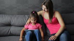 有儿童用途的妇女片剂坐长沙发 有儿童用途的母亲片剂坐沙发 股票视频