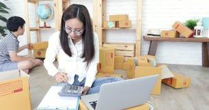 有儿童男孩工作的年轻亚裔妇女和包装泰国张贴箱子
