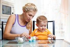 有儿童男孩的母亲装饰复活节彩蛋 免版税库存照片