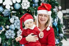 有儿童男婴的母亲有在红色服装和圣诞老人帽子的蓝眼睛的由新年树 免版税库存照片