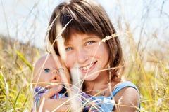 有儿童的玩偶的可爱的美丽的女孩 免版税库存照片