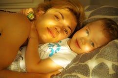 有儿童谎言的妇女在床上 免版税库存照片