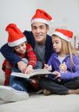 有儿童阅读书的父亲在圣诞节期间 免版税图库摄影