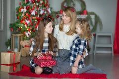 有充分庆祝接近xmas树的两个女孩女儿的逗人喜爱的令人敬畏的白肤金发的母亲妈妈新年圣诞节在时髦的d的玩具 库存照片